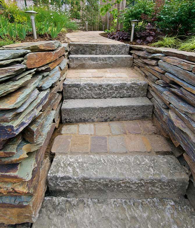 Natuurstenen, verwerkt tot een trap in een natuurlijke vorm in een tuin in Maastricht