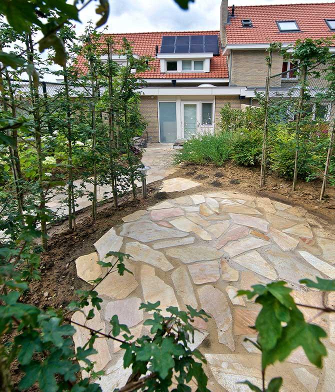 Riant zitgedeelte van natuurstenen in een natuurlijke tuin in Maastricht